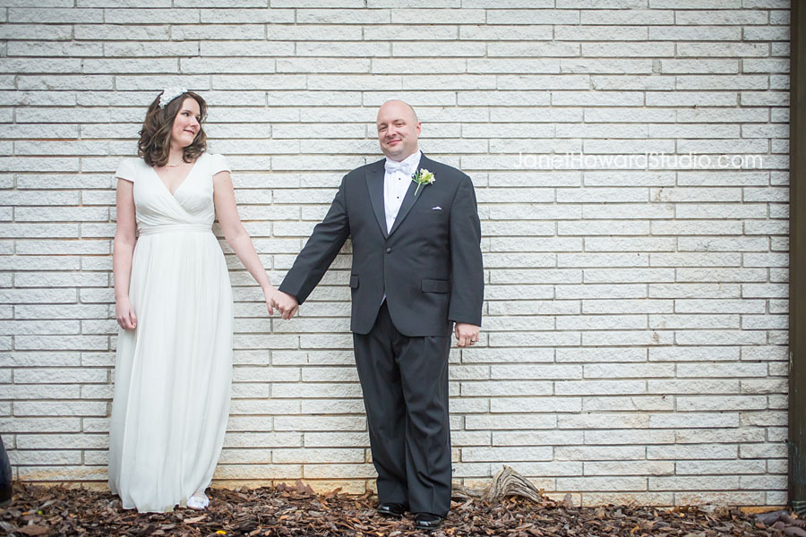 Bride and groom on white brick wall